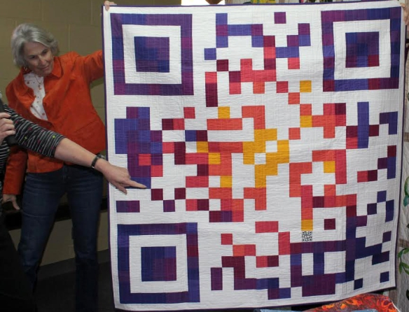 A new friend holding up one of my quilts at a recent guild talk